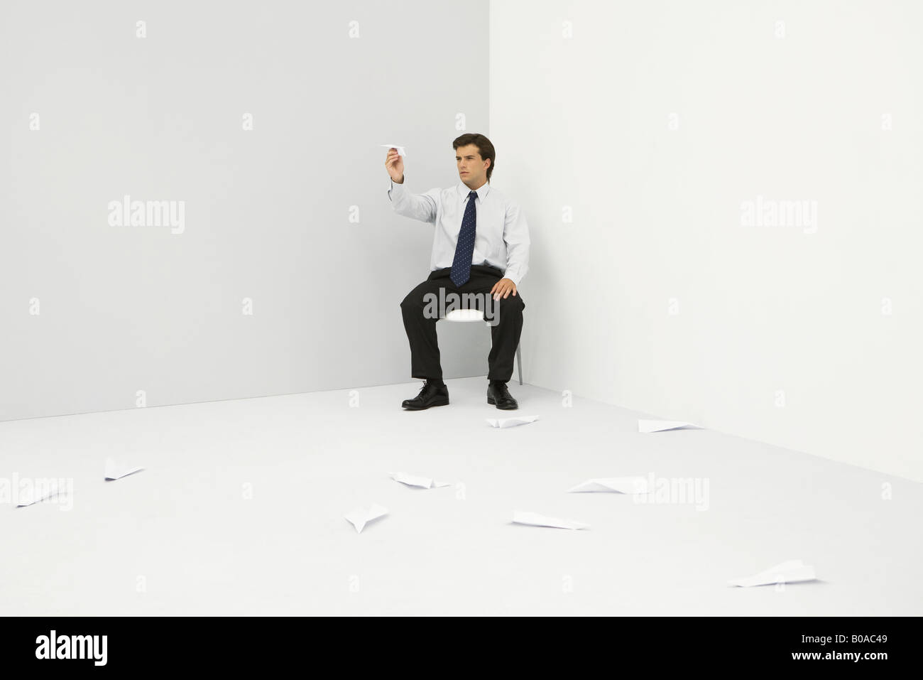 Male professional sitting in corner, throwing paper airplanes - Stock Image