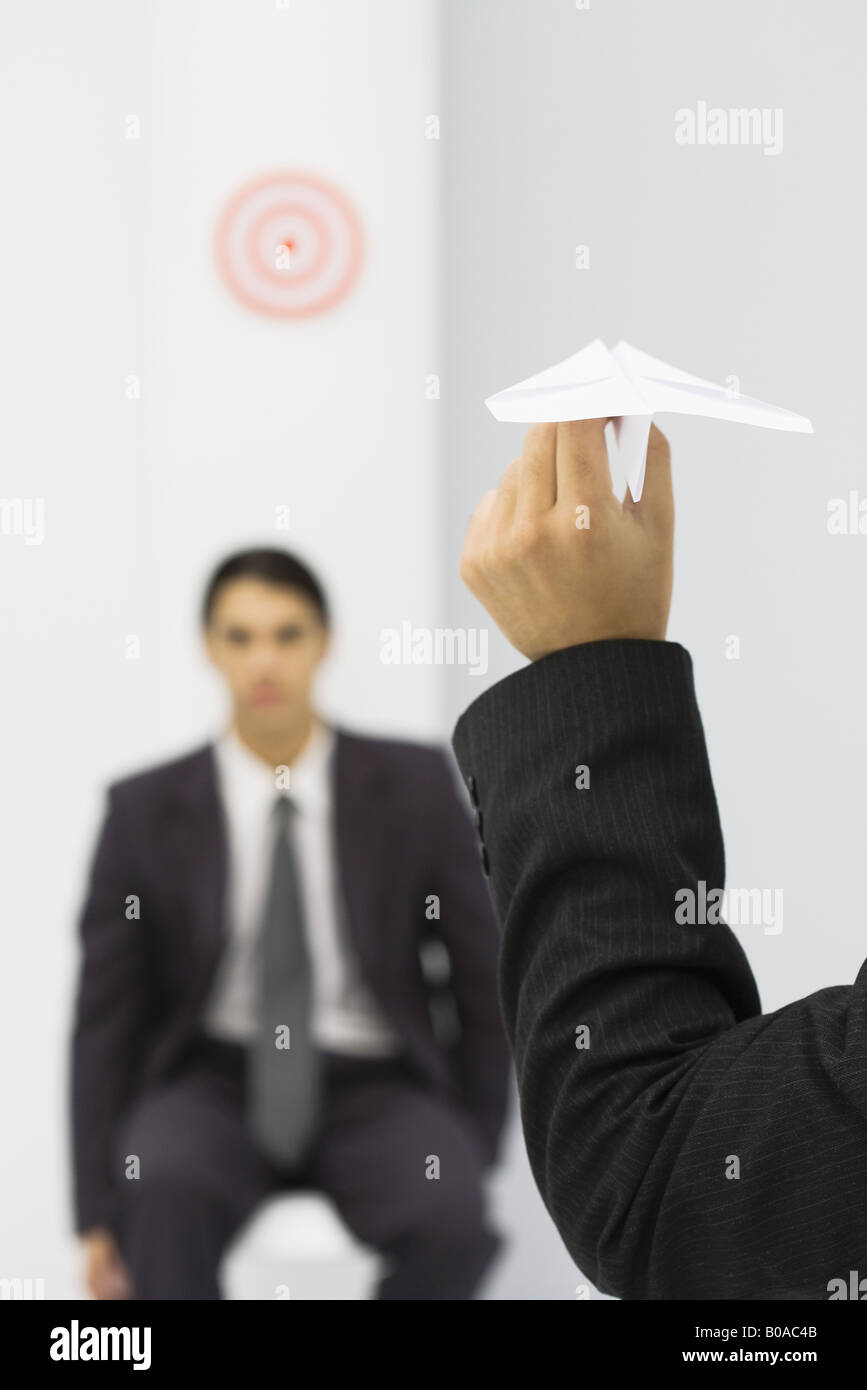 Man holding paper airplane, aiming at target of colleague's head, cropped view - Stock Image