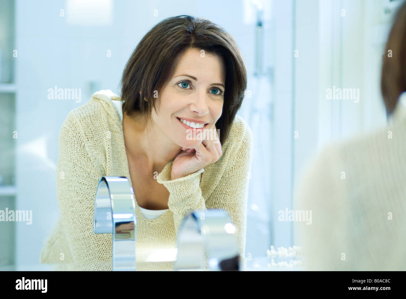 Woman smiling at self in bathroom mirror - Stock Image