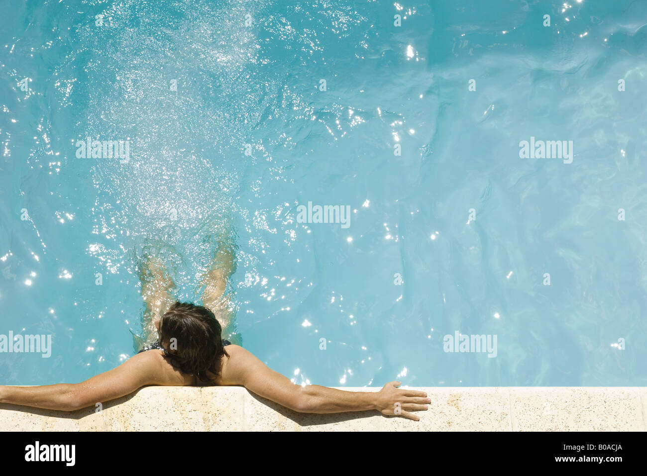 Man in swimming pool, holding on to edge, high angle view - Stock Image