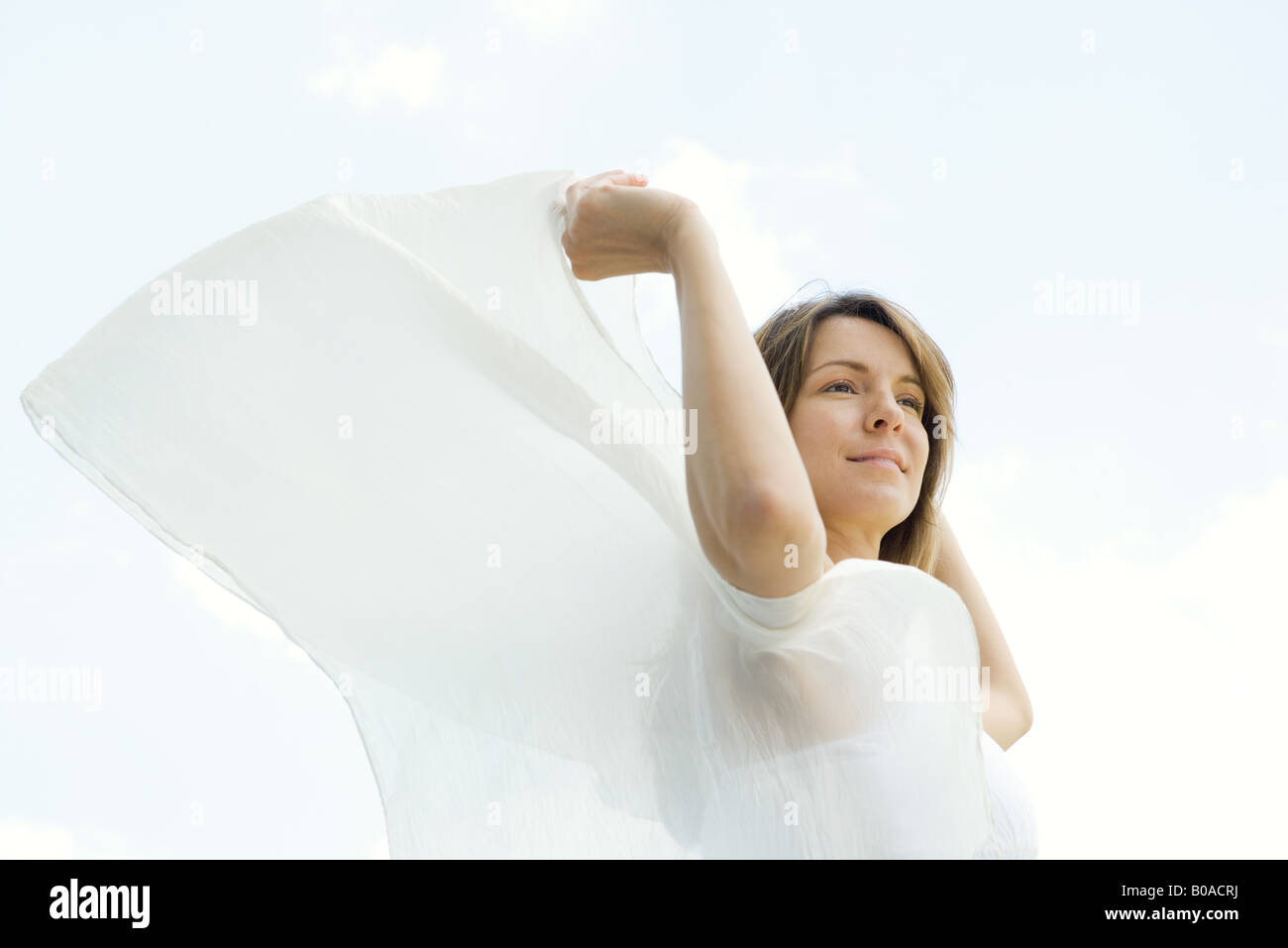 Woman outdoors, holding shawl in wind, looking away, low angle view - Stock Image
