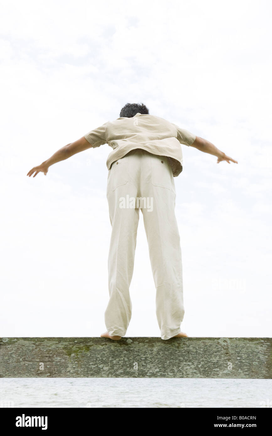 Man standing on ledge with arms out, leaning forward, rear view - Stock Image