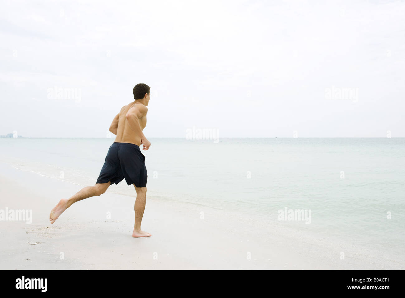 Man running at the beach, side view - Stock Image