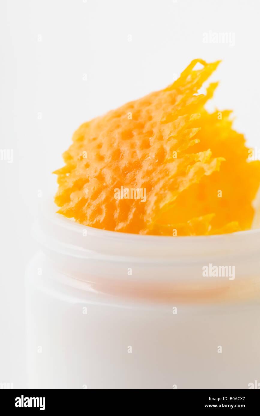 Orange rind in cosmetic jar, close-up - Stock Image