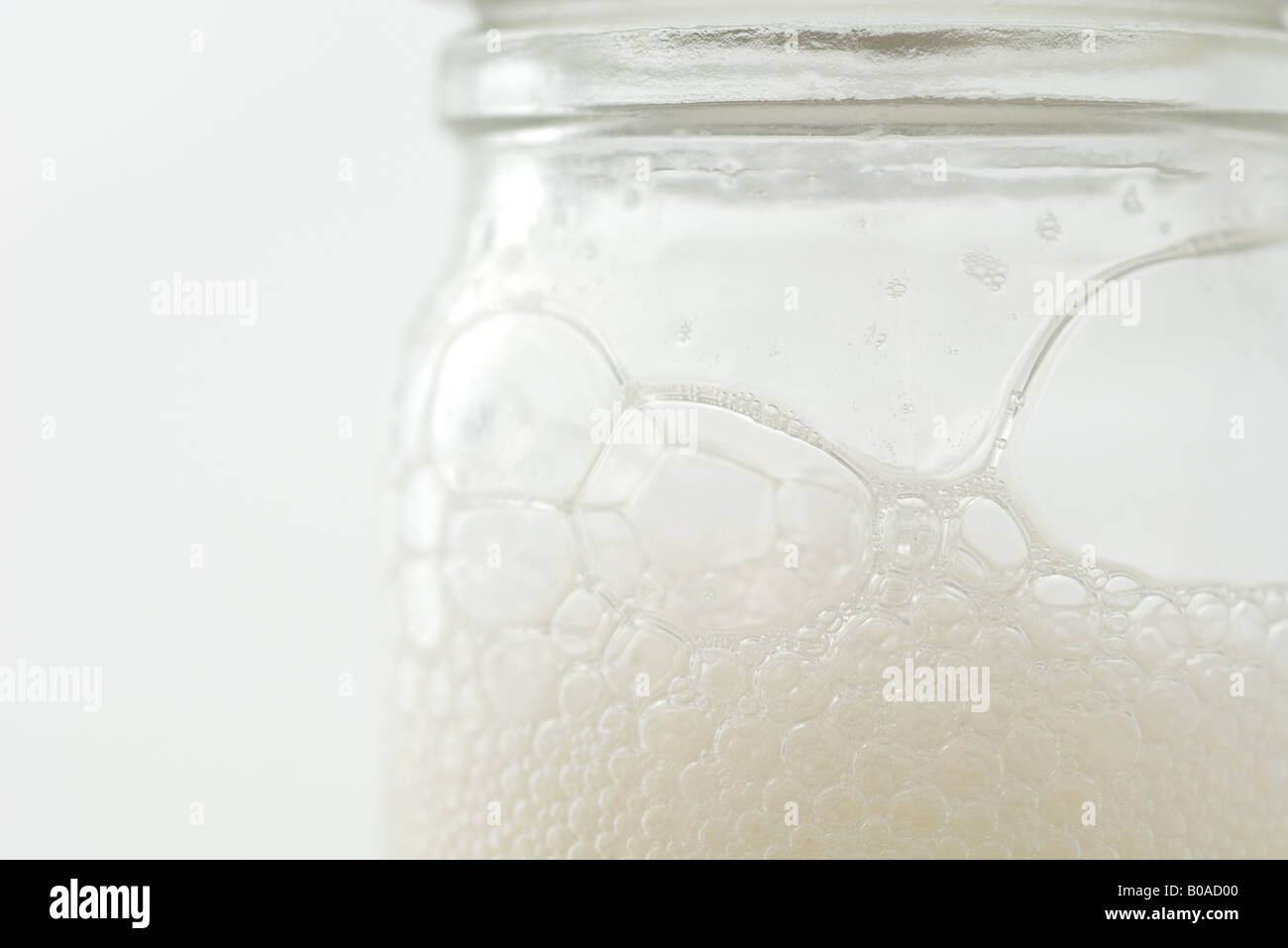 Glass jar with soap suds, extreme close-up - Stock Image
