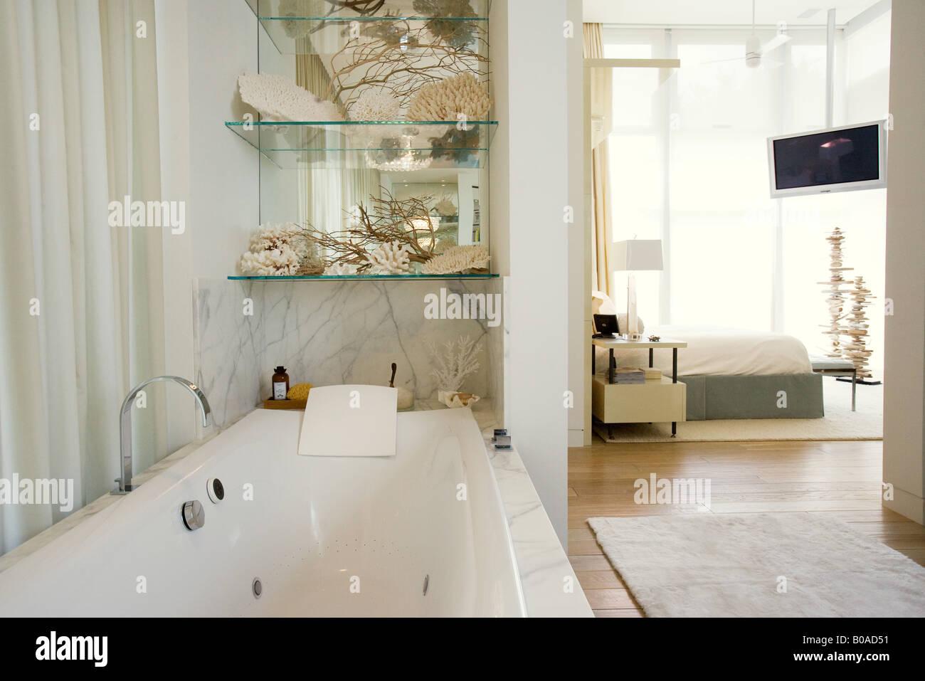 Luxury hotel bathroom with large bathtub, bedroom in background ...