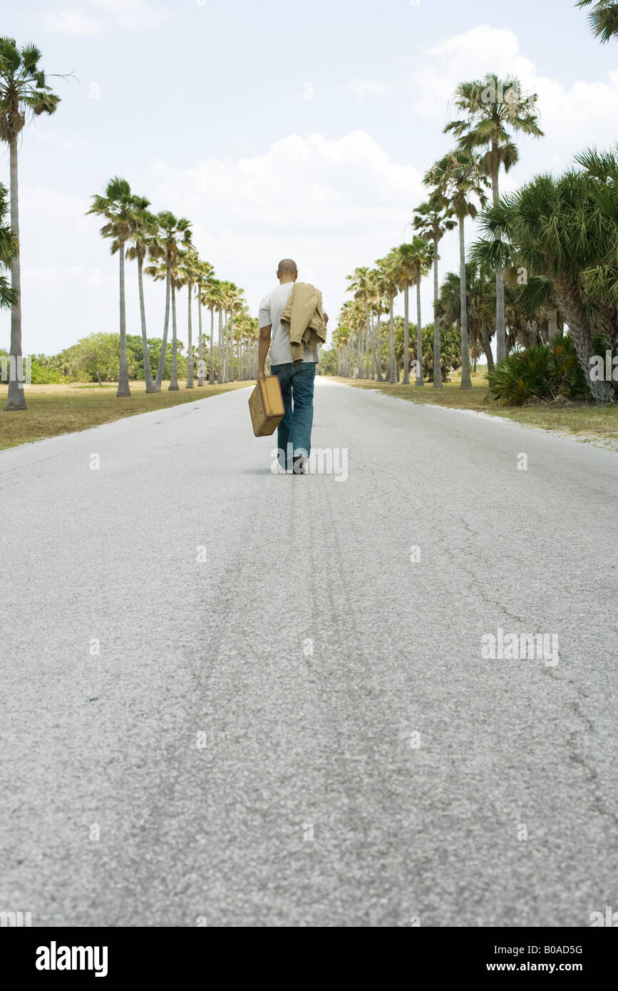 Man walking in center of road, carrying suitcase and jacket, rear view - Stock Image