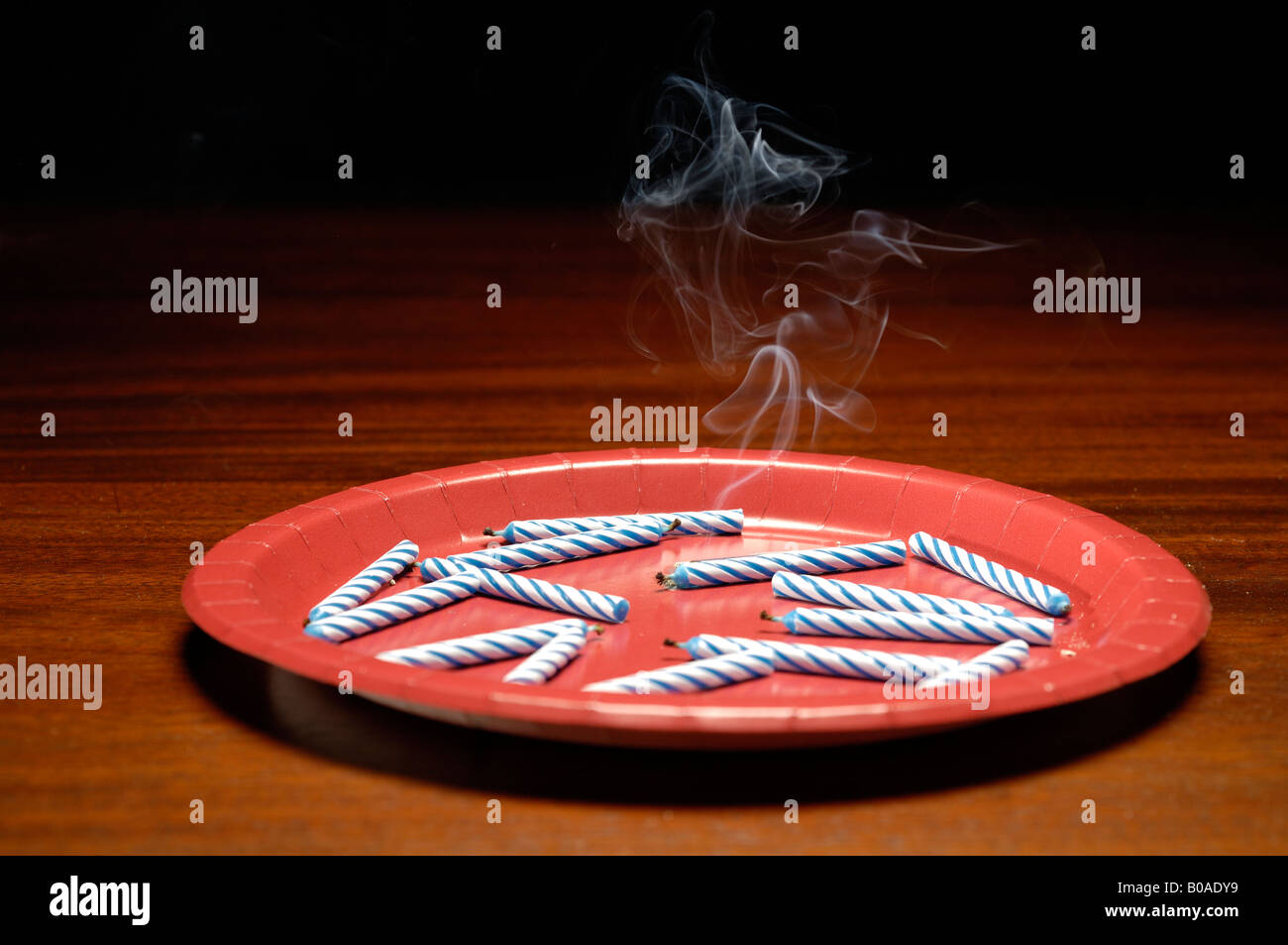 Burnt out candles with smoke on a red plate wood table. - Stock Image