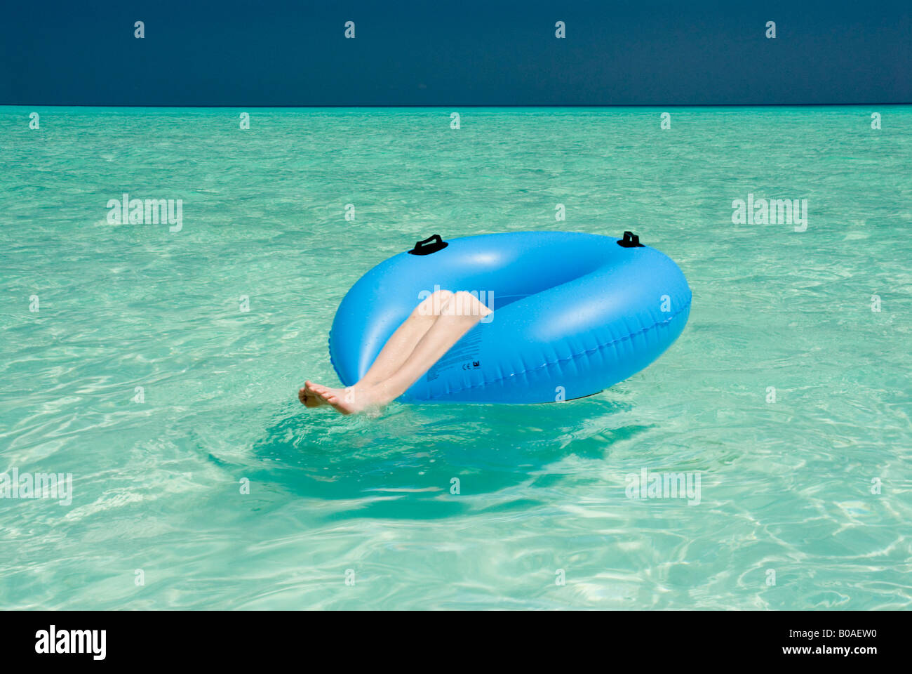 Teenage boy one person lying in blue rubber ring relaxed chilled out blue lagoon blue sky Oscar Hanna MR - Stock Image