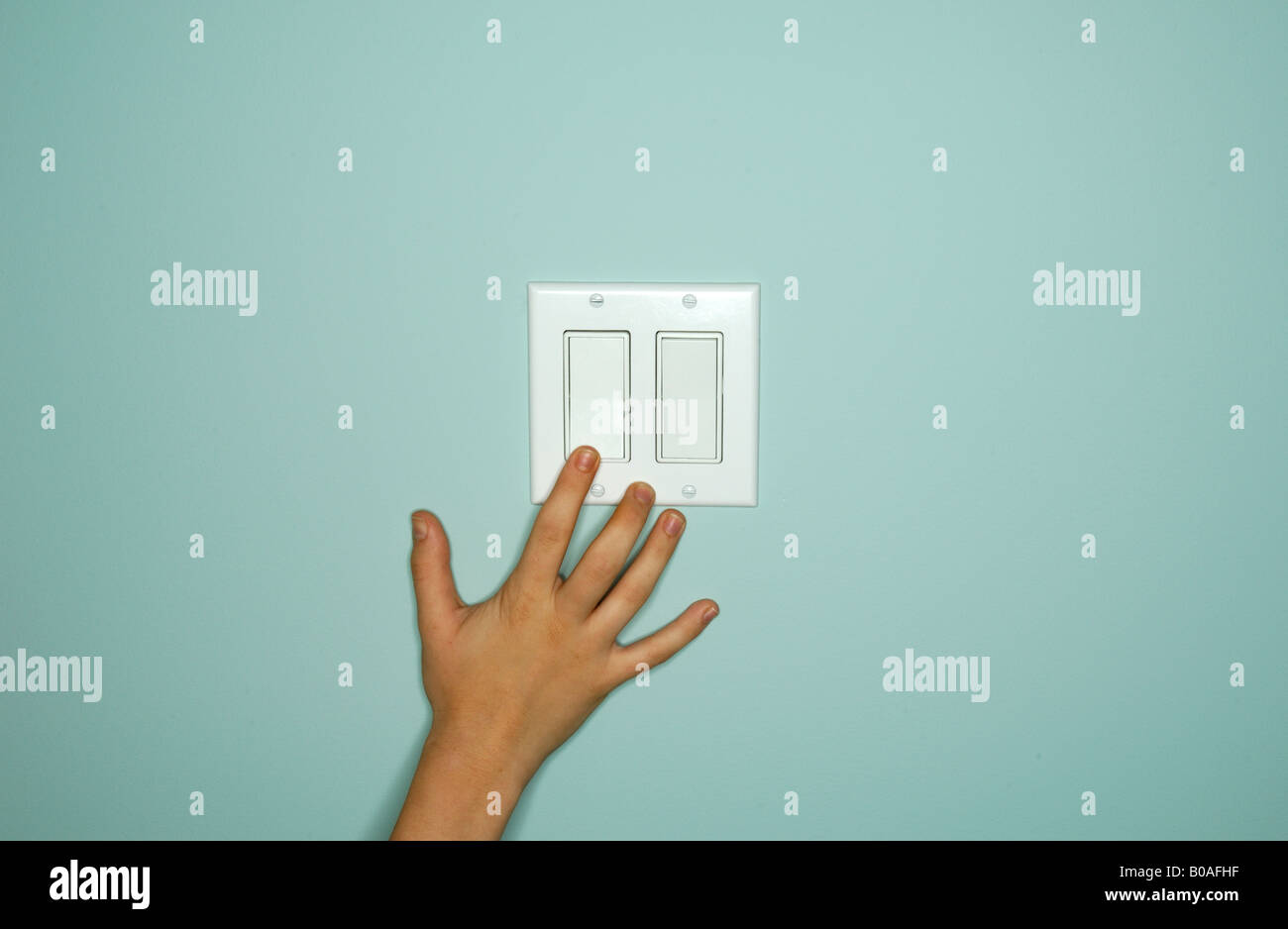 A hand touching or reaching a light switch control - Stock Image