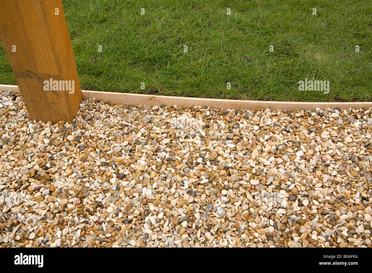 Gravel path with wooden lawn edging and pergola base Stock
