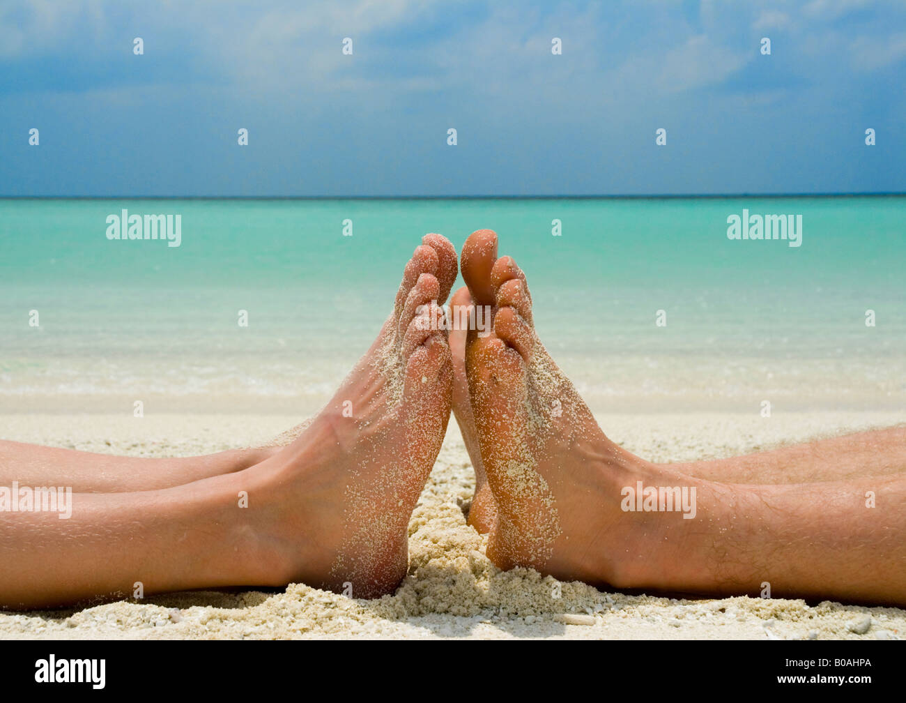 Two sets of feet and legs lying on tropical sandy beach blue sea blue sky - Stock Image