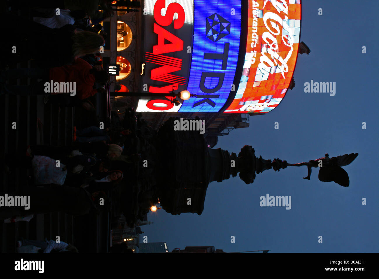 The bright neon lights of Picadilly Circus silhouetting the Eros fountain. - Stock Image