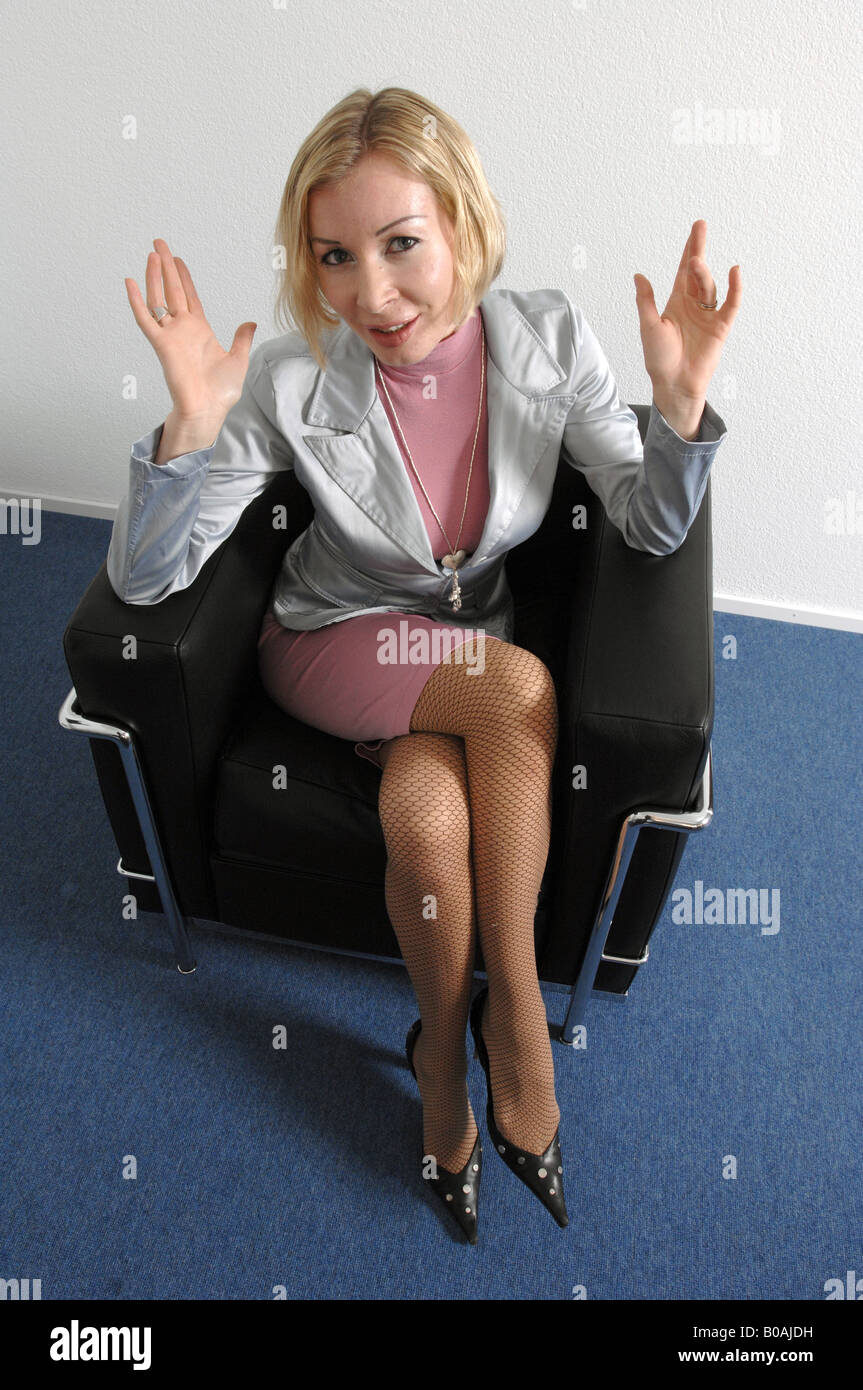 Blond woman sitting in a chari - Stock Image