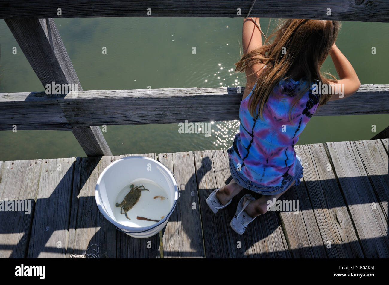 Young girl crab fishing from pier at Hunting Island South Carolina, USA. Stock Photo