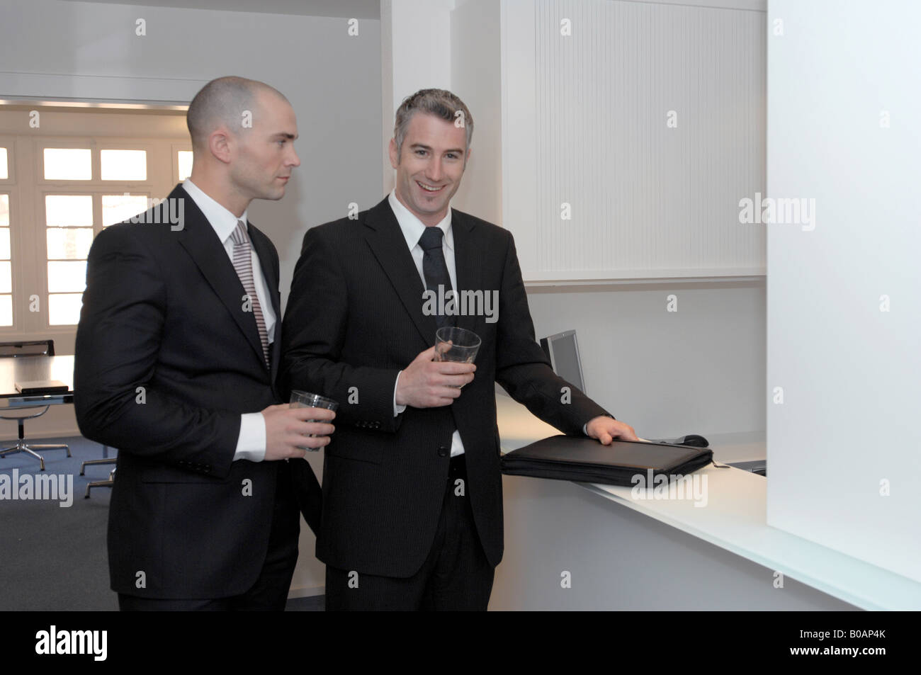businessmen at a reception desk - Stock Image
