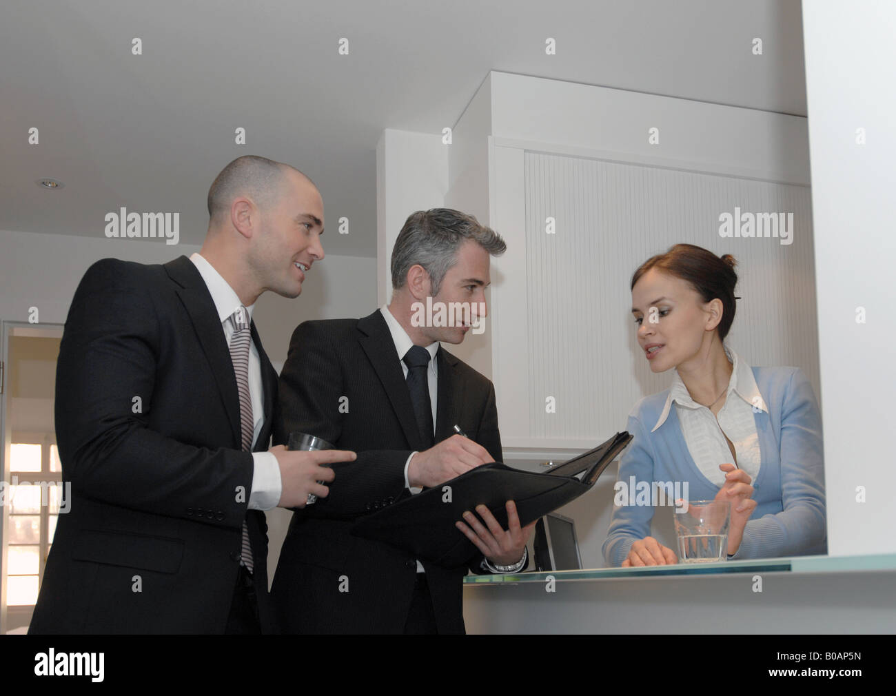 businessmen talking to a receptionist - Stock Image