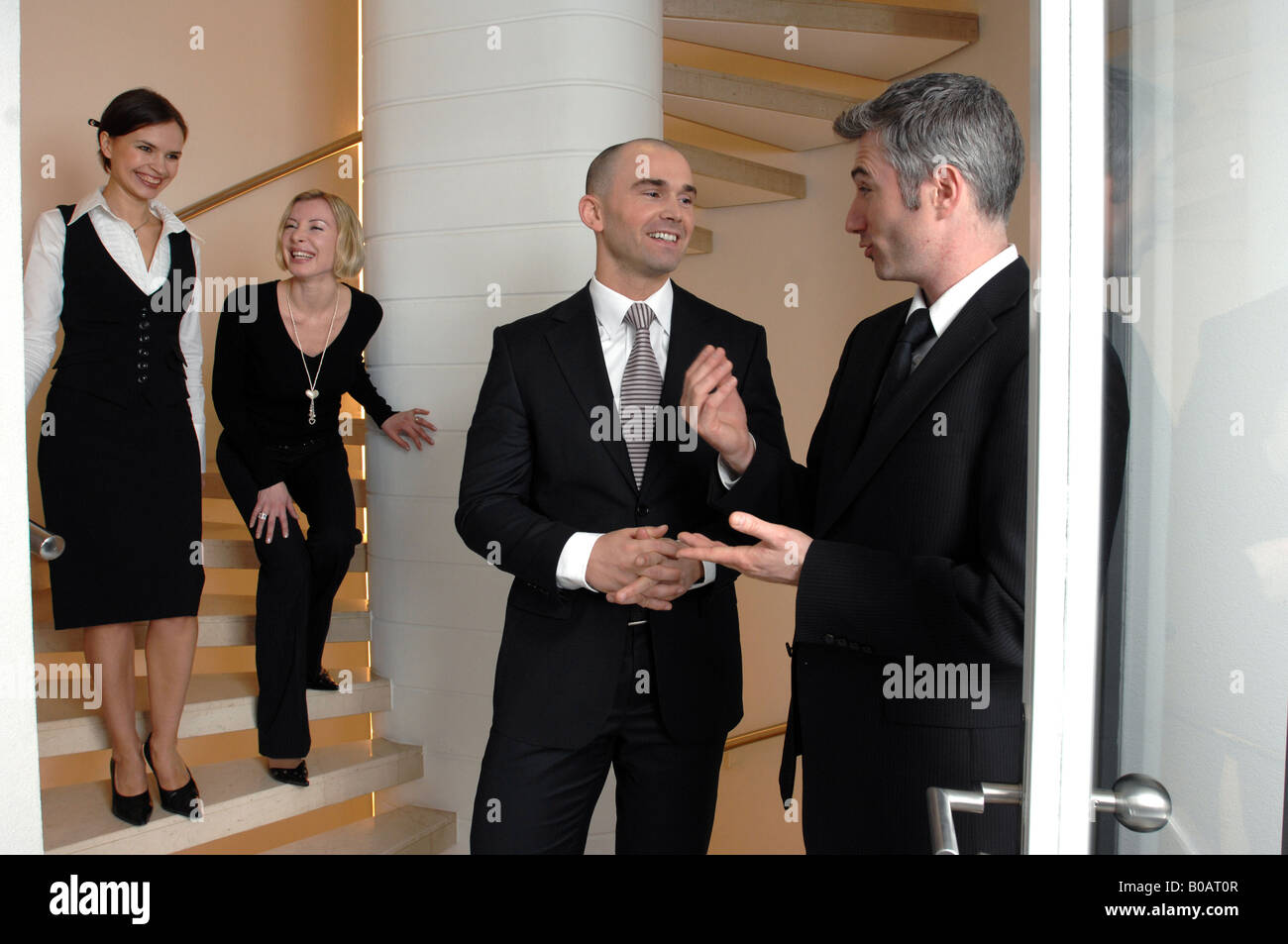 business people talking inside an office building - Stock Image