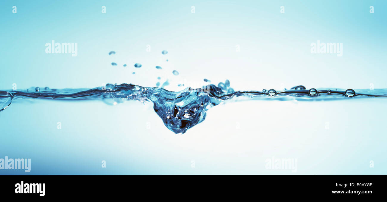 close-up water level with drop and bubbles - Stock Image