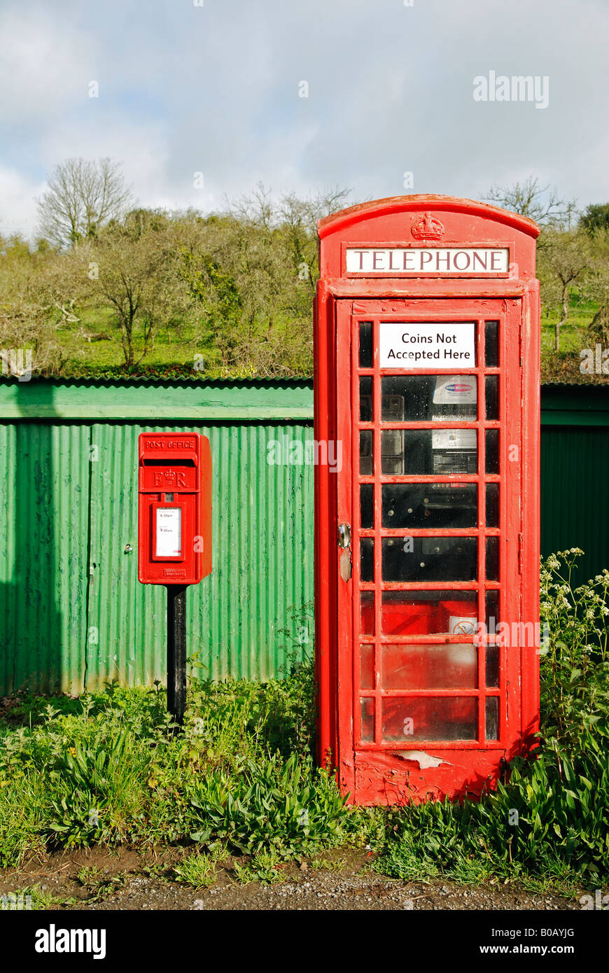 a british red telephone box next to a small postbox in cornwall,england - Stock Image