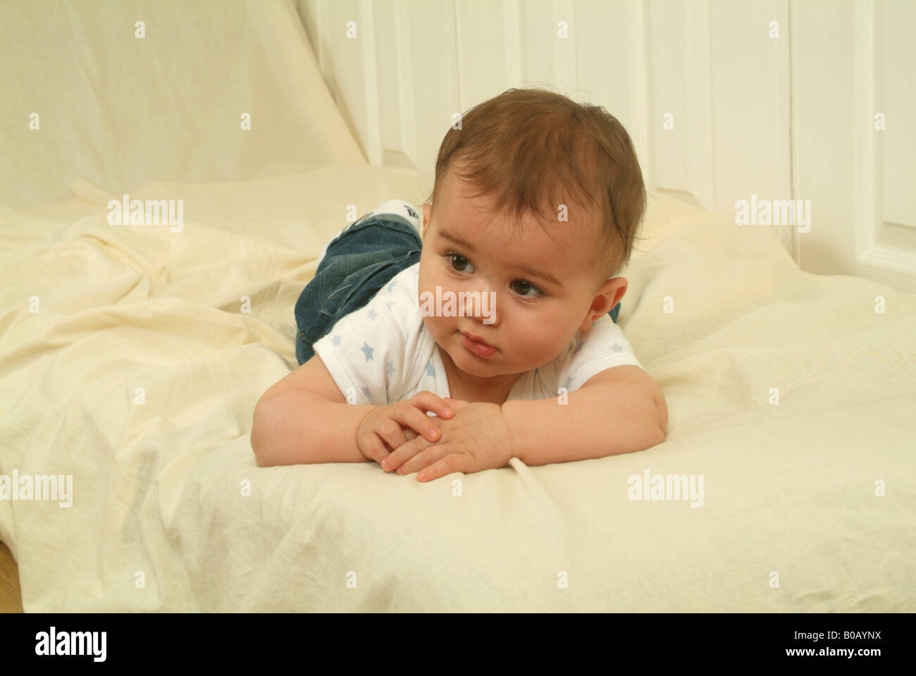 An eight month old baby boy lying on his front on a white couch and clasping