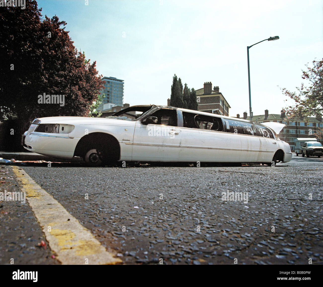 limousine burnt out in road - Stock Image