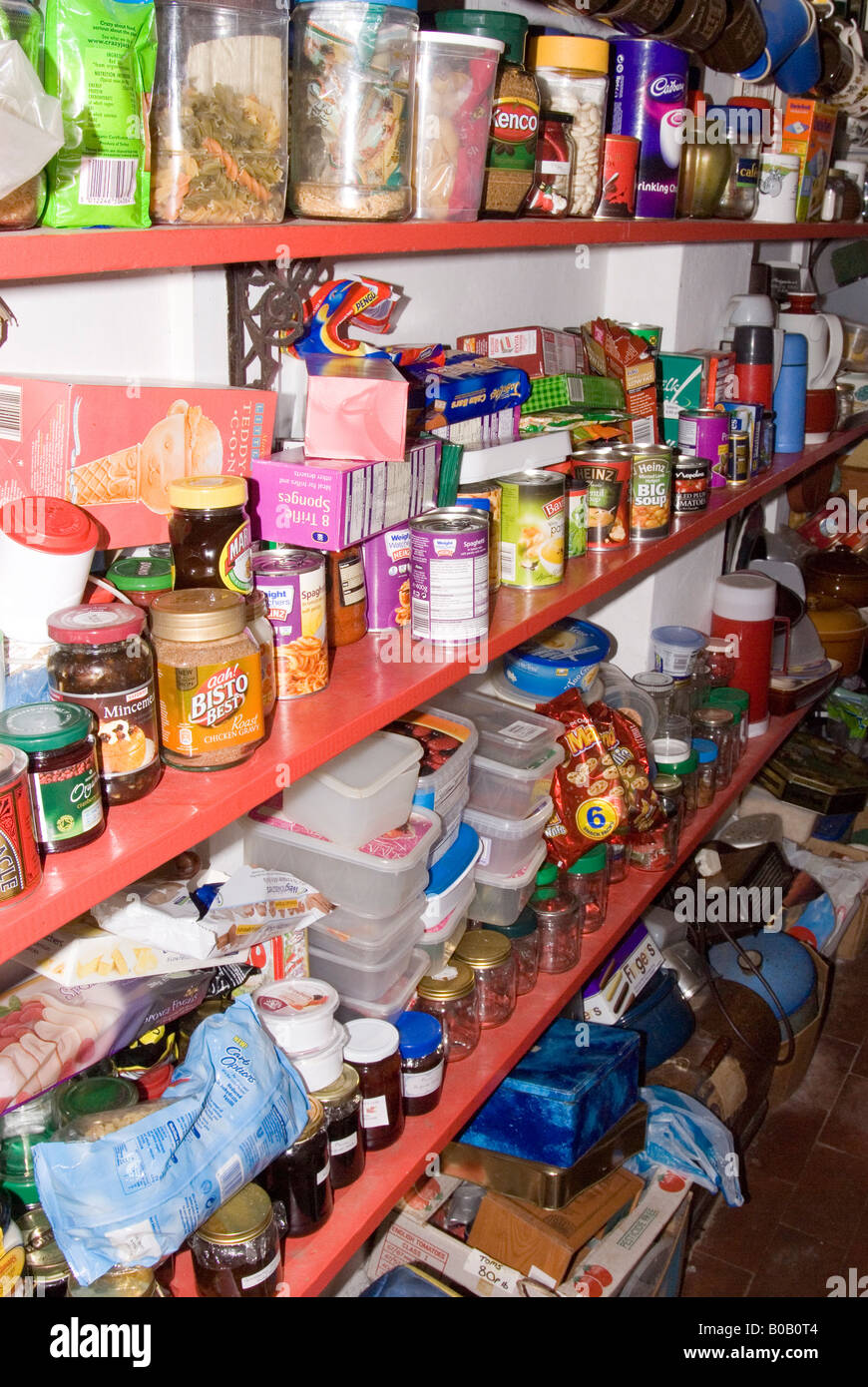 Untidy Larder full of tins of food and hoarded items - Stock Image
