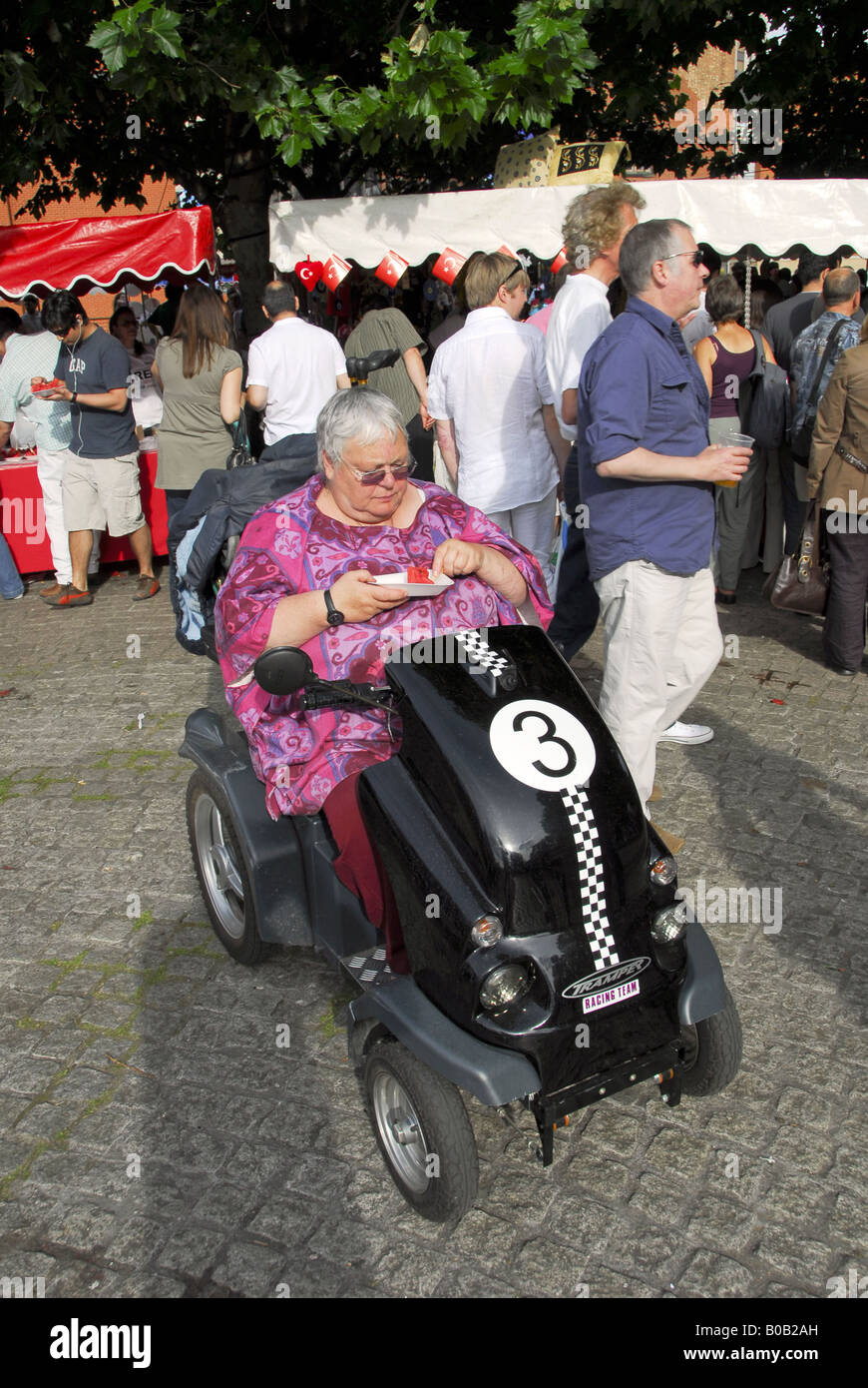 LADY IN HER 70`s EATING HER TAKEWAY WHILE IN HER WHEELCHAIR - Stock Image