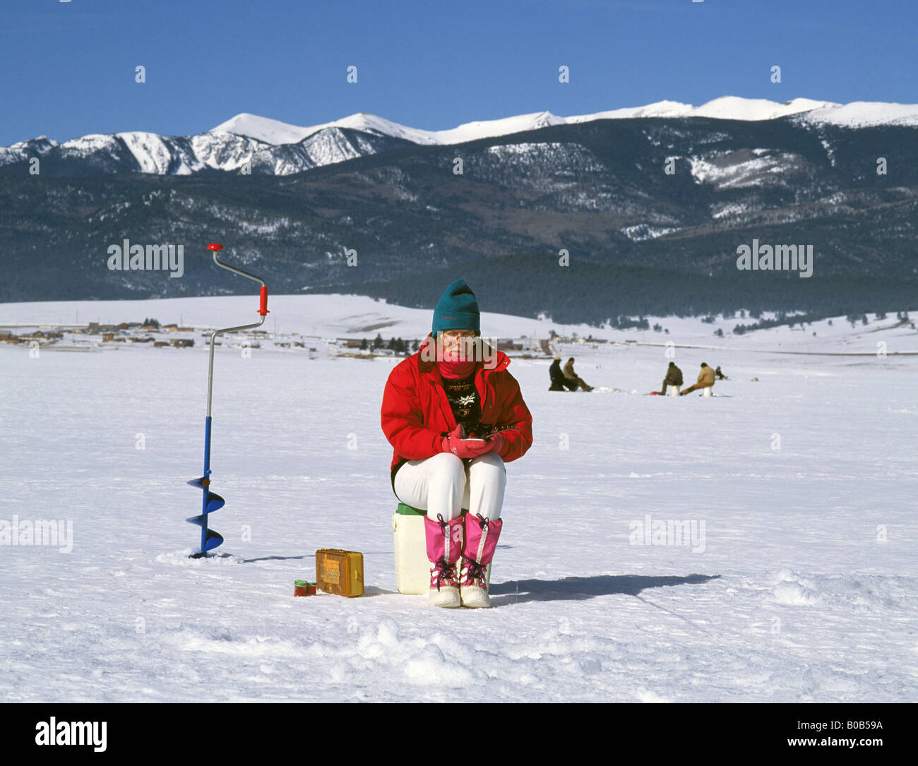 A woman with an ice auger ice fishing on Eagle Nest Lake in the
