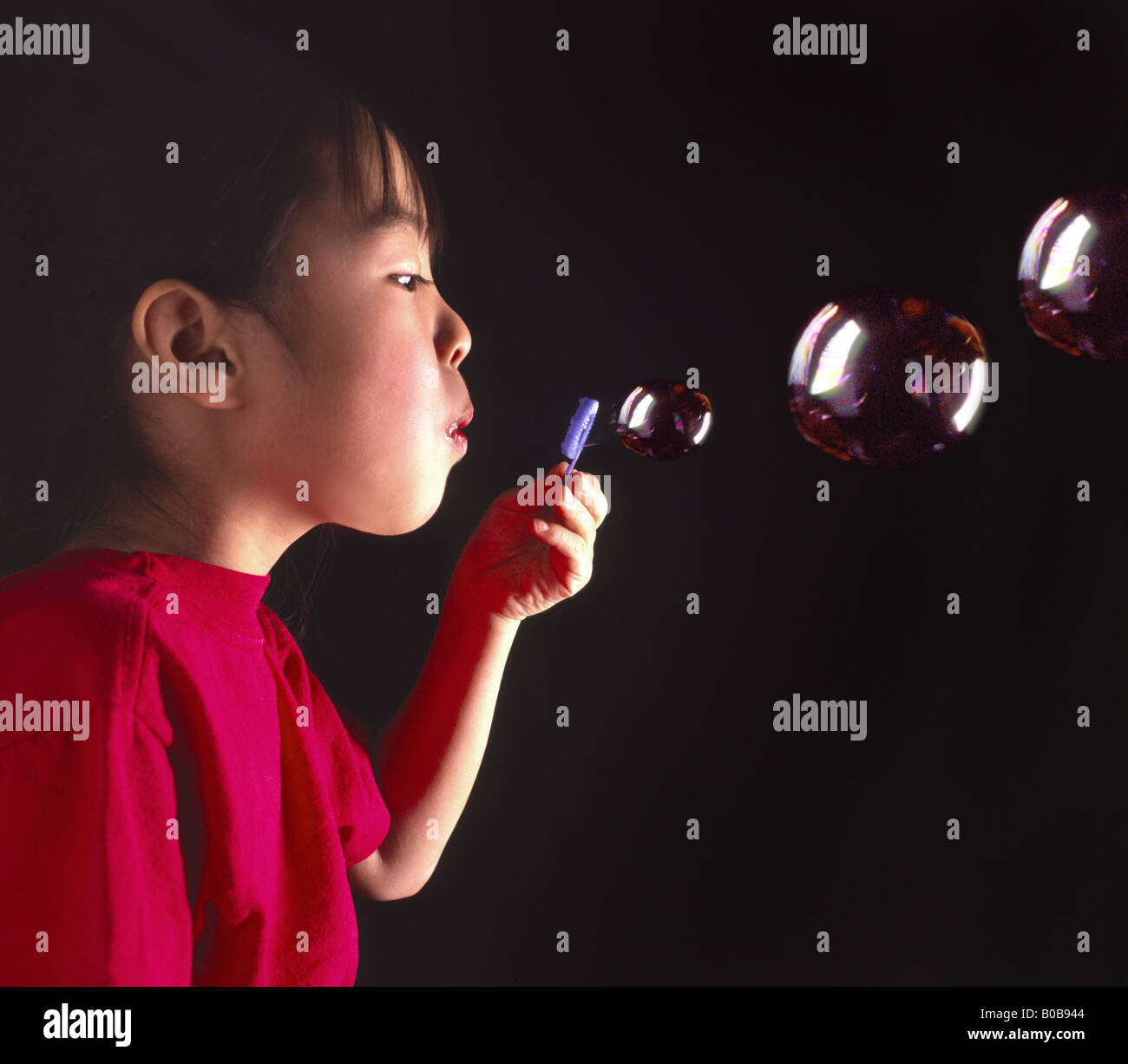 young oriental girl blowing bubbles - Stock Image
