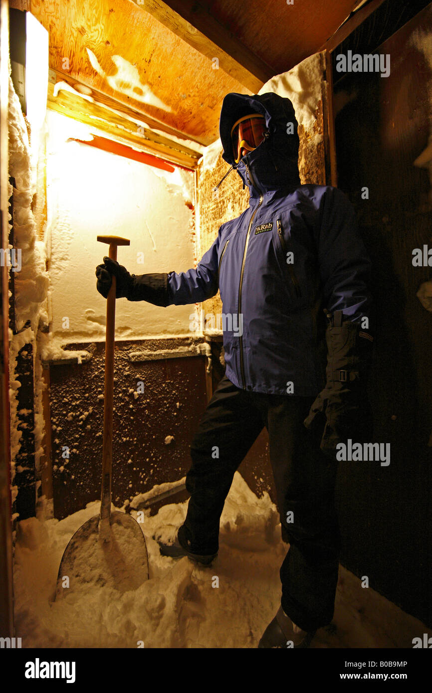 Tourist snowed in and about to dig himself out of the Guesthouse in Ittoqqortoormiit, East Greenland - Stock Image
