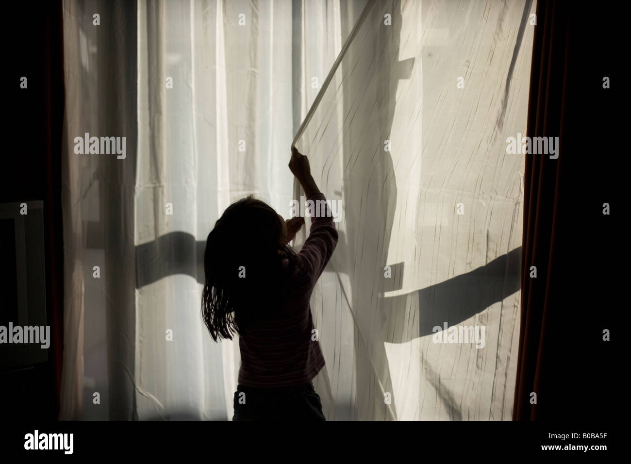 Four year old girl pulls closed the net curtains of a motel room in Wellington New Zealand - Stock Image