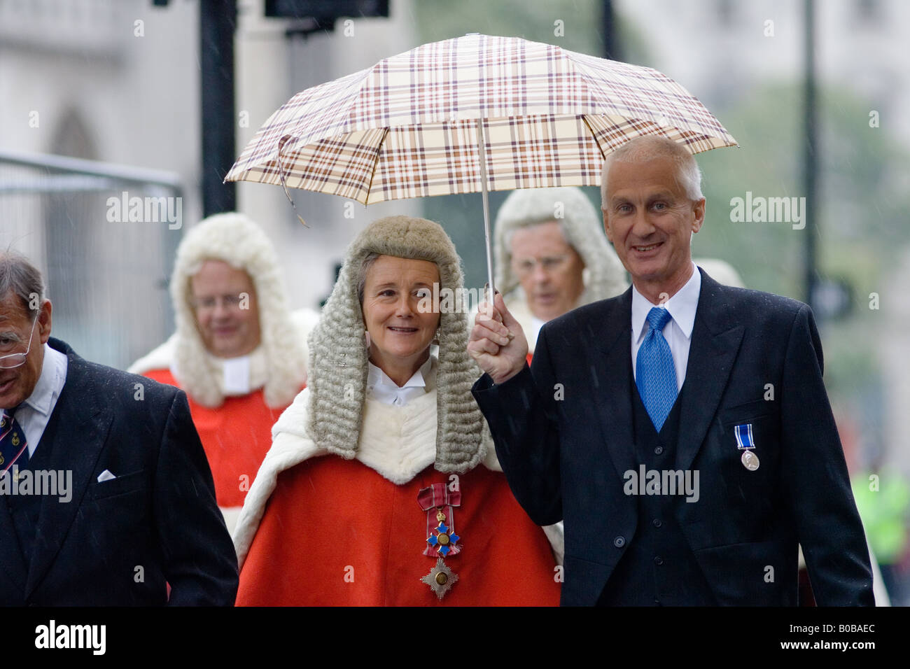 Lady judge sheltered from rain in Judges Procession from Westminster Abbey London England United Kingdom - Stock Image