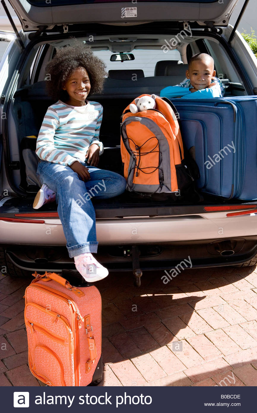 Brother and sister  in back of car with luggage, smiling, portrait Stock Photo