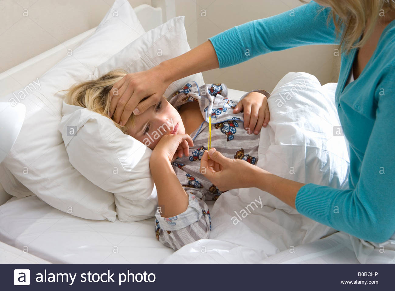 Mother taking daughter's  temperature, close-up - Stock Image