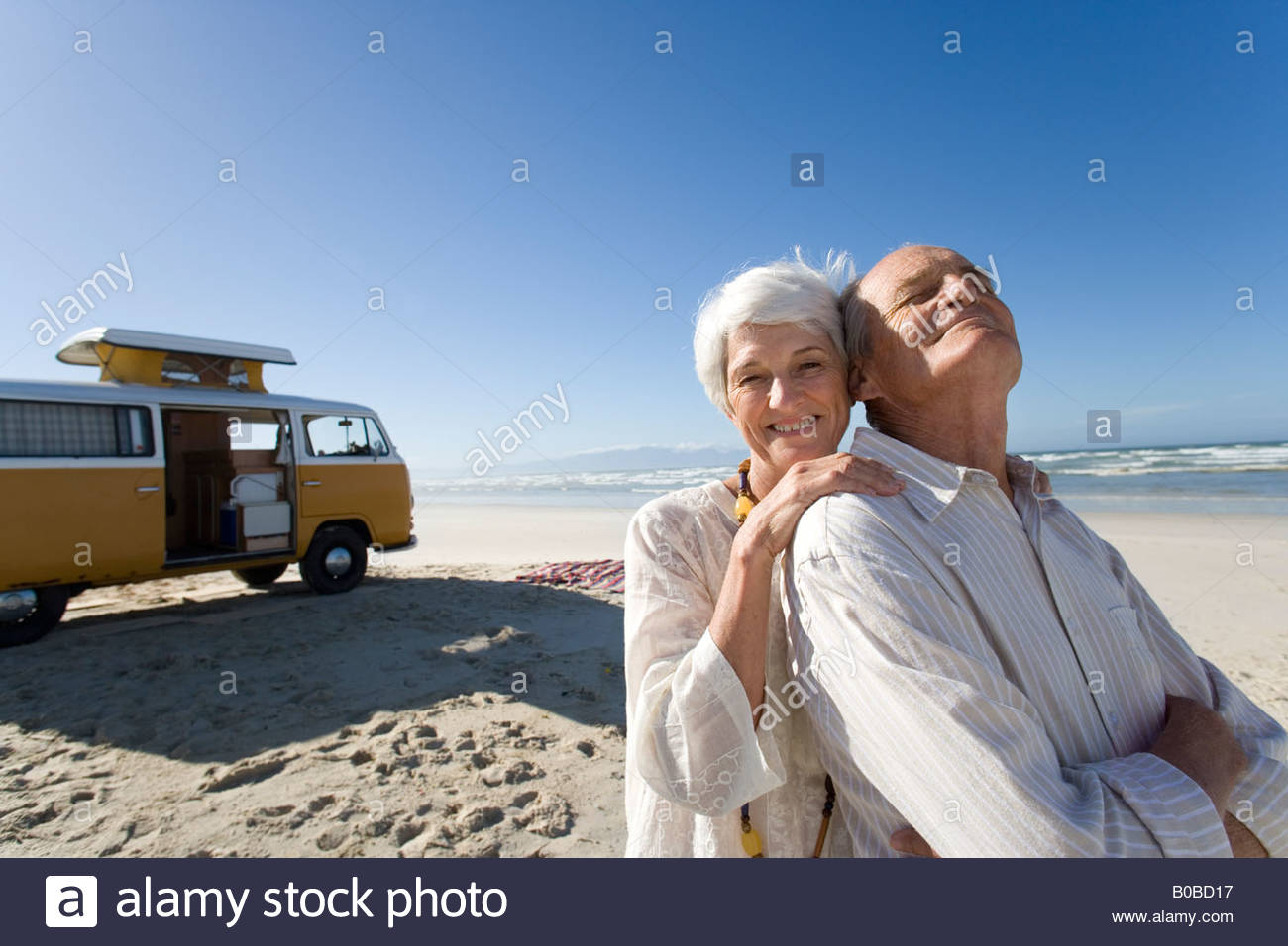 Senior woman embracing senior man from behind on beach by camper van, smiling, portrait - Stock Image