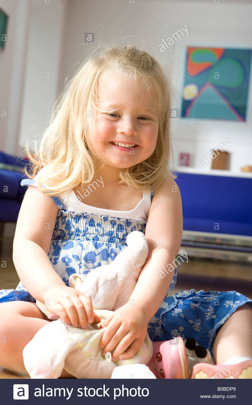 Girl 2-4 on floor with toy, smiling, close-up - Stock Image
