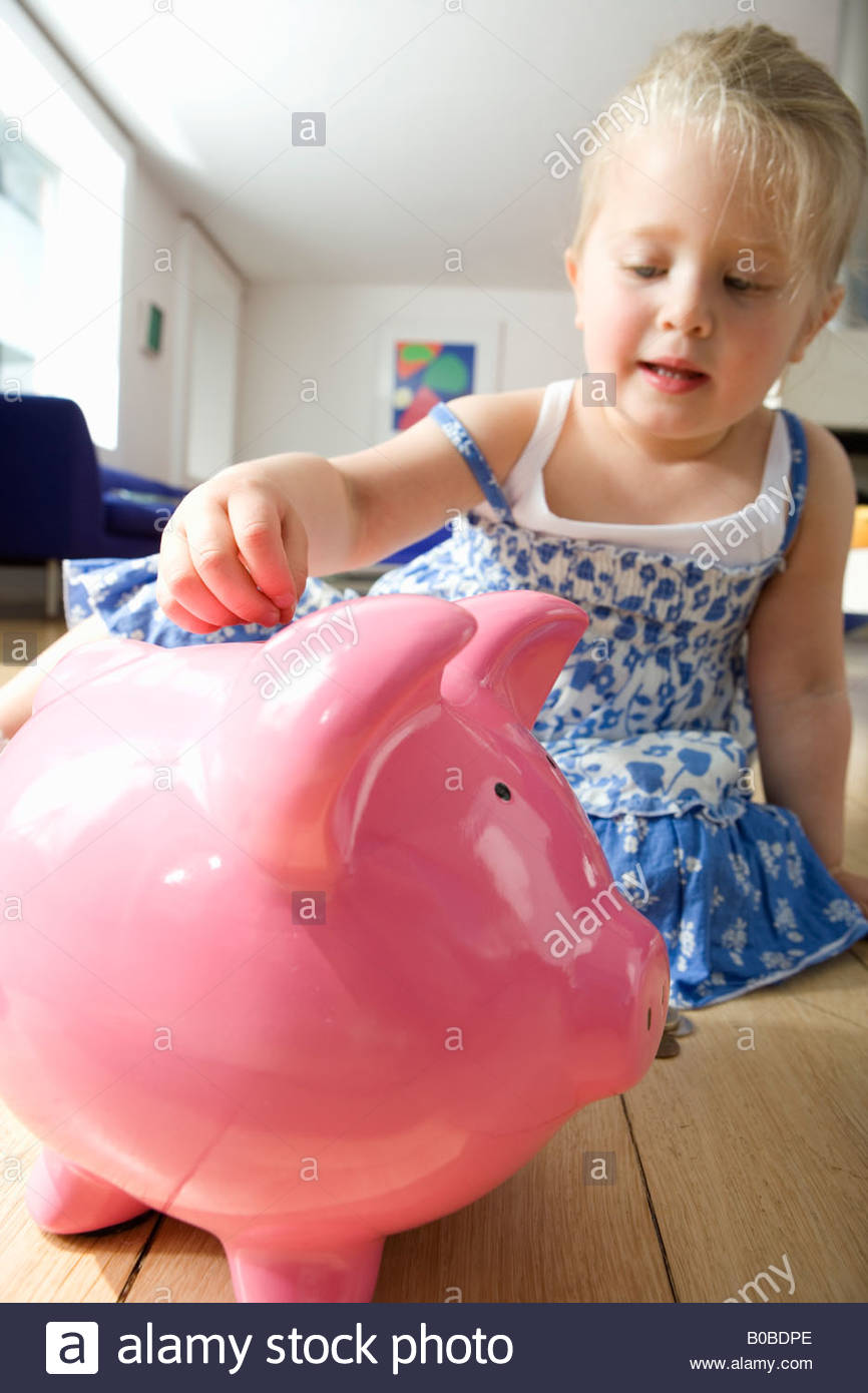 Girl 2-4 putting coin in piggy bank, low angle view - Stock Image