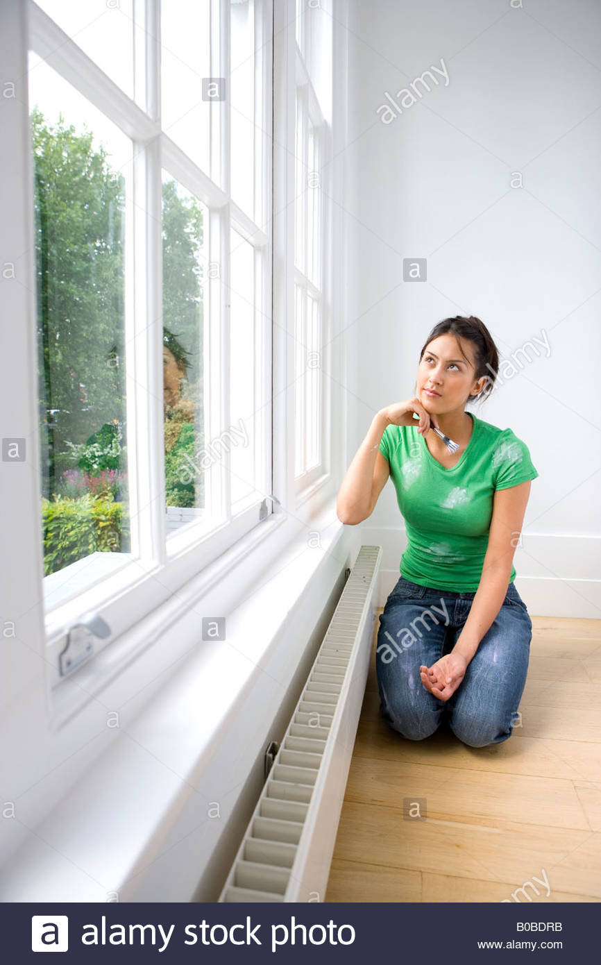 Young woman with paintbrush kneeling on floor, looking at window - Stock Image