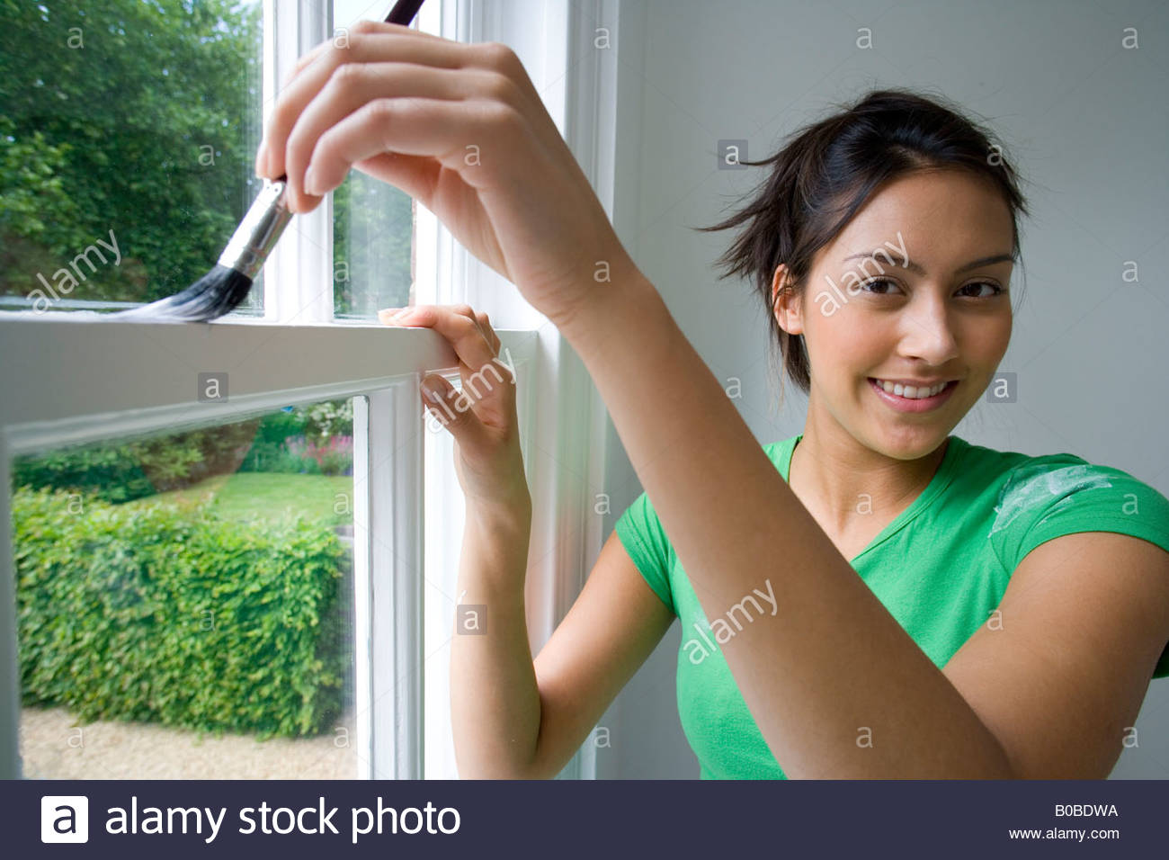 Young woman painting window frame, smiling, portrait, close-up - Stock Image