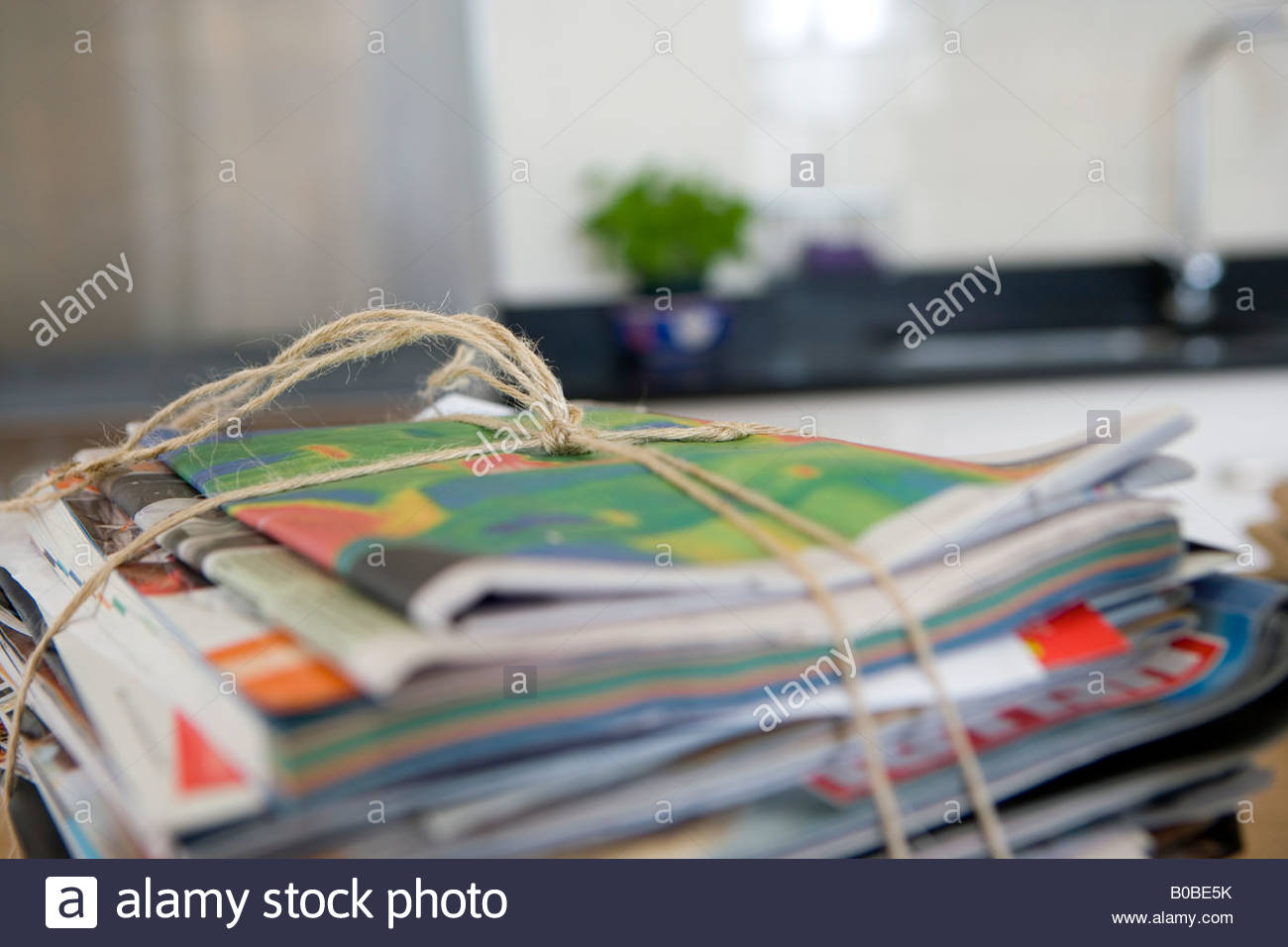 Bundle of newspapers tied with string, close-up - Stock Image