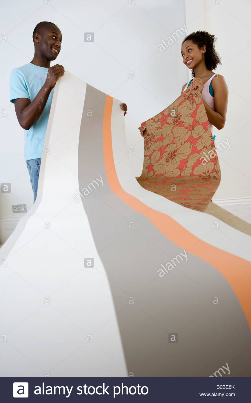 Young couple looking at wallpaper, smiling at each other - Stock Image