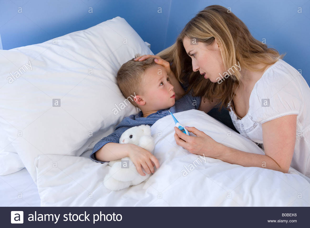 Boy  in bed, mother taking temperature, elevated view - Stock Image