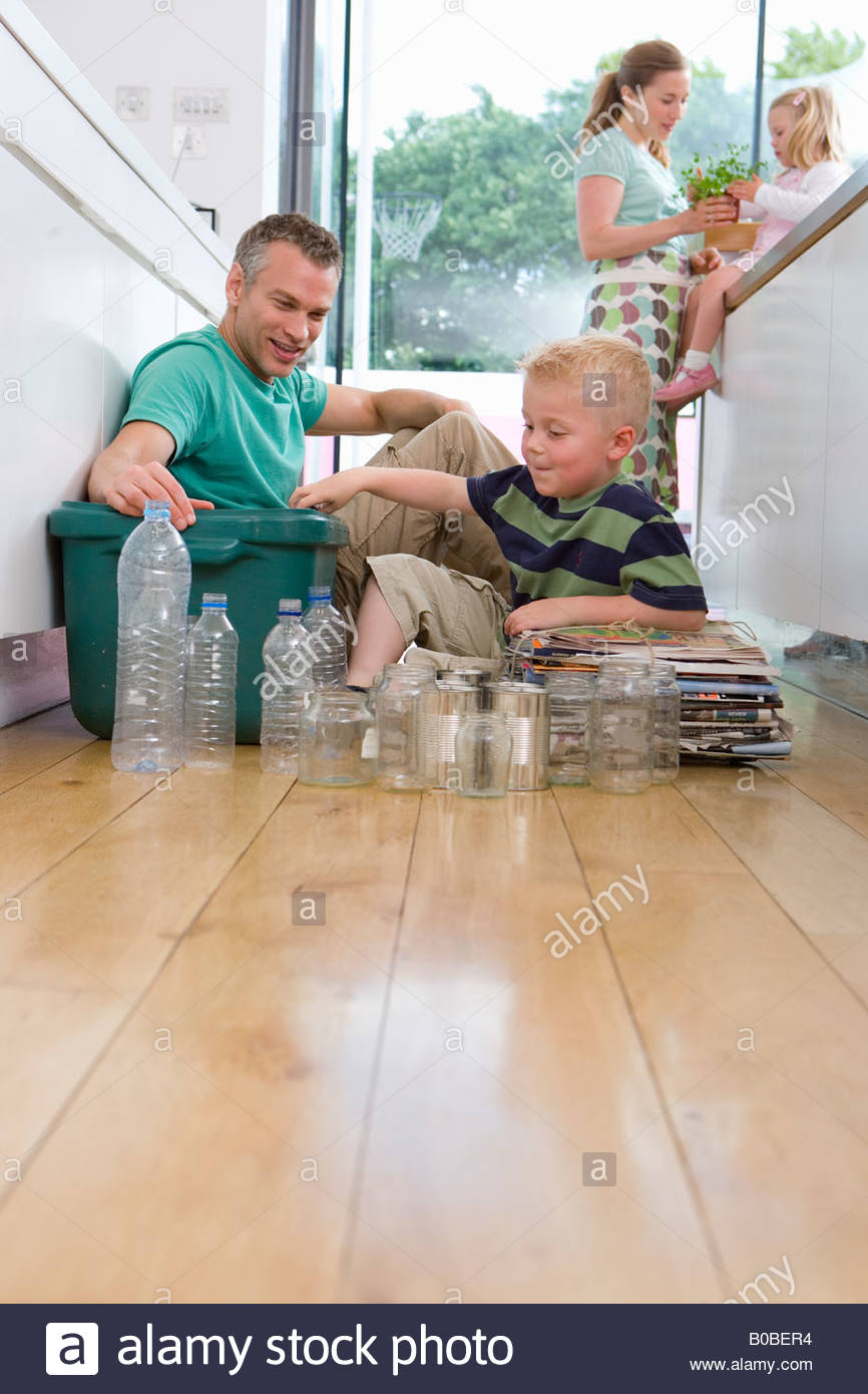 Family of four in kitchen, father and son 2-4 putting recycling into bin, low angle view - Stock Image
