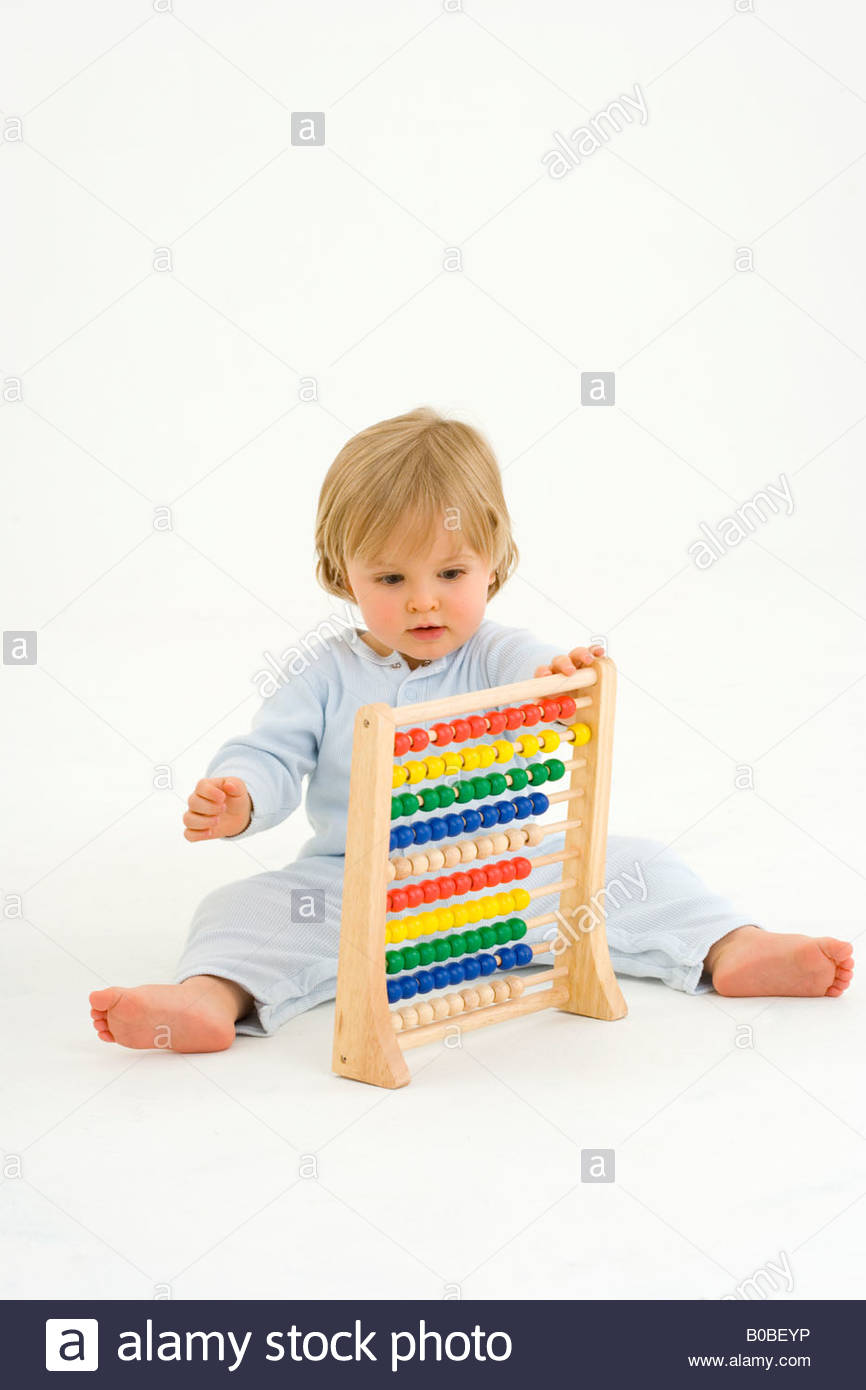 Baby boy 6-9 months playing with abacus - Stock Image