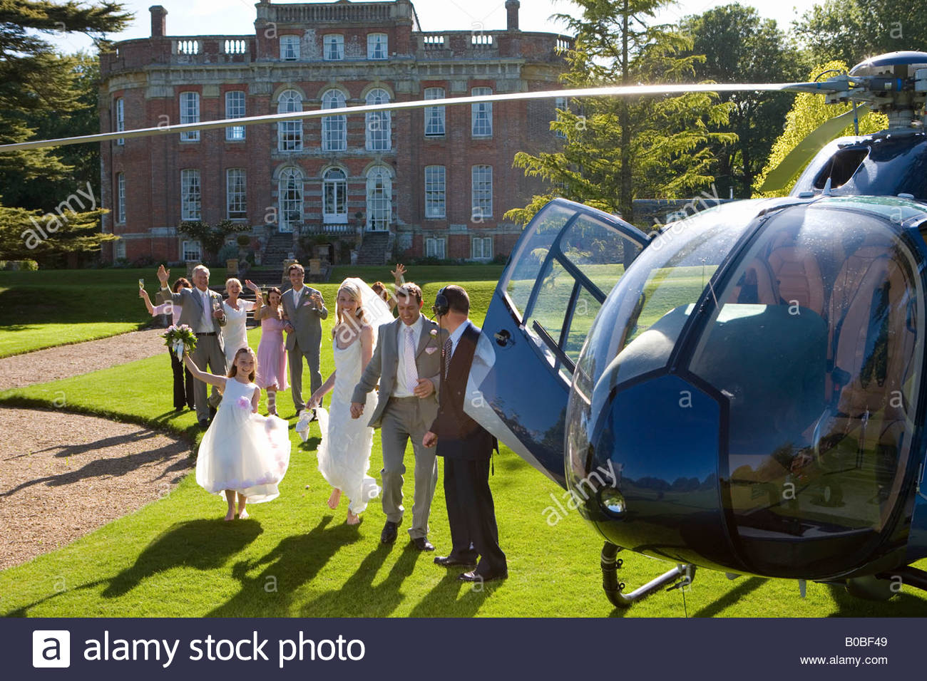 Wedding guests waving at bride and groom by helicopter - Stock Image