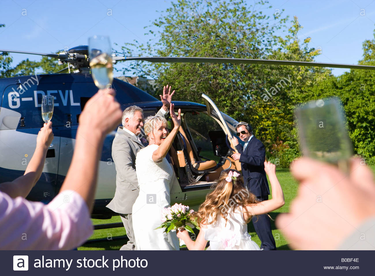 Bride and groom by helicopter waving to wedding guests - Stock Image