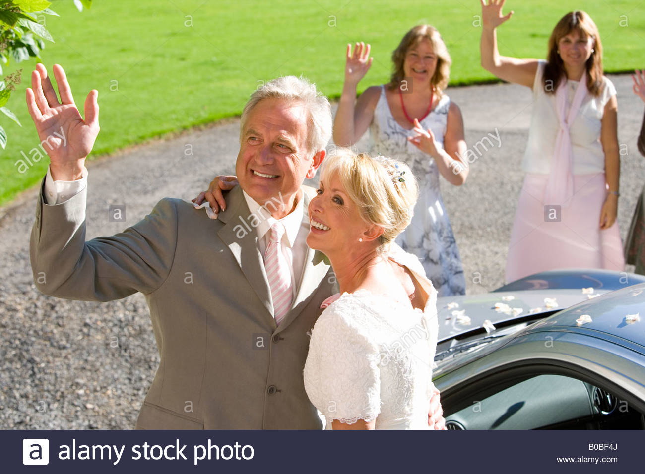 Bride, groom, and guests waving, smiling, elevated view - Stock Image