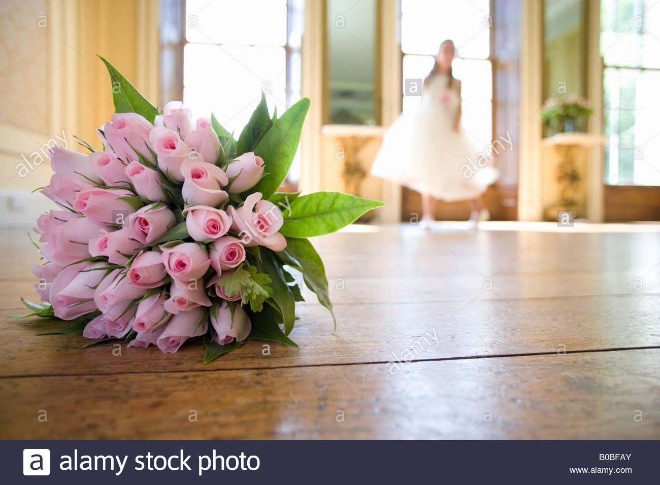 Wedding bouquet of flowers on floor, flower girl in background Stock ...