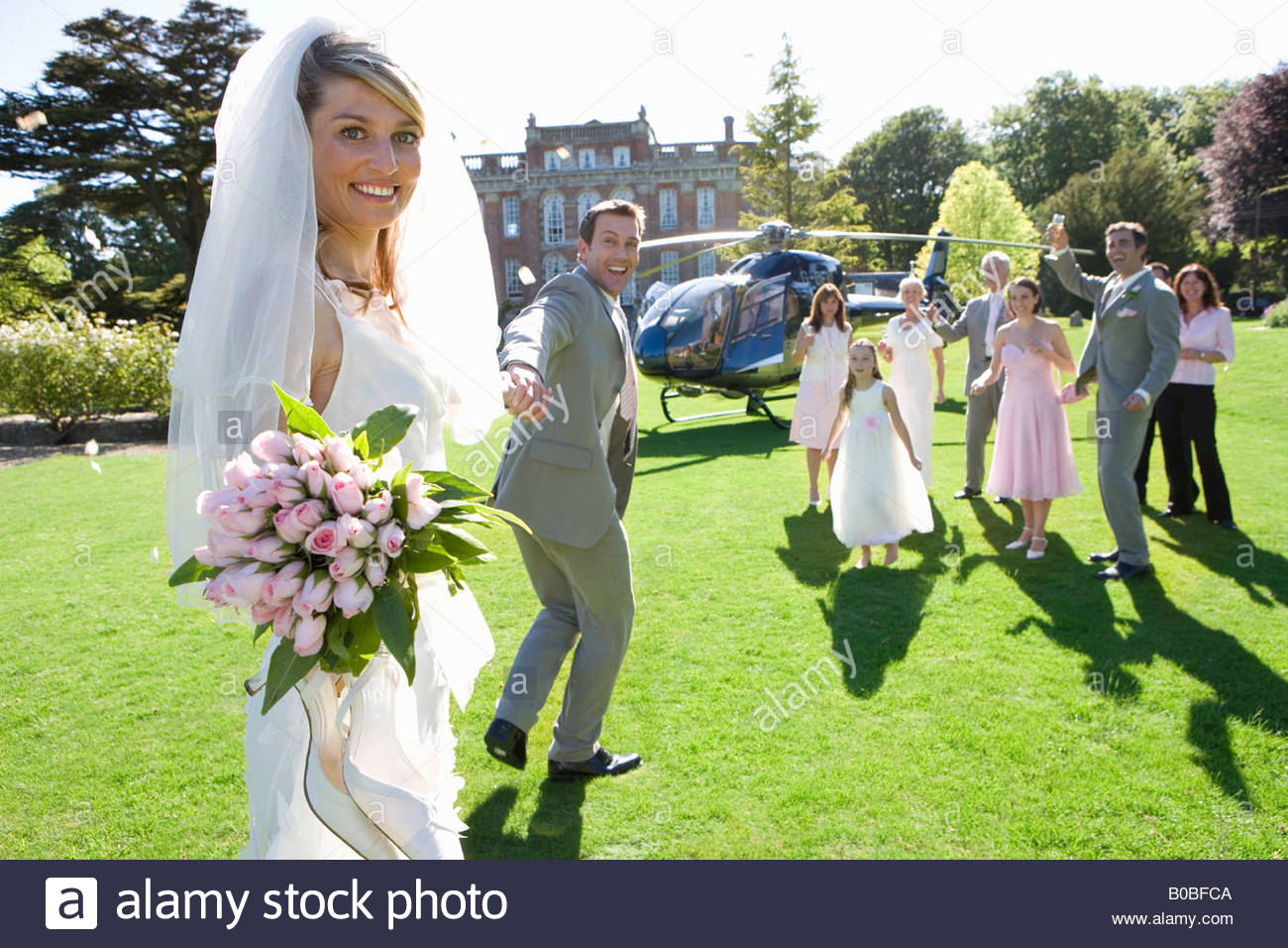 Groom leading bride towards helicopter, smiling, portrait of bride - Stock Image